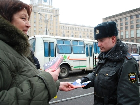 Activist handing out copies of the Russian constitution to police. Source: Kasparov.ru