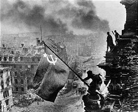 Red army soldiers raising the Soviet flag on the roof of the Reichstag in Berlin